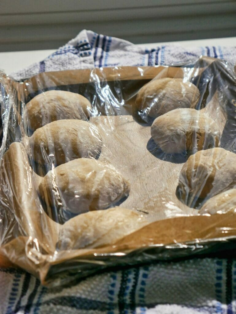 brioche buns with saran wrap over them