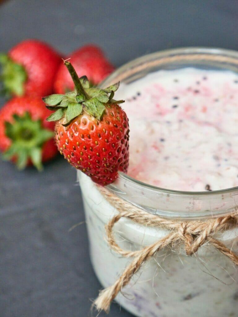 strawberry on rim of overnight oats jar